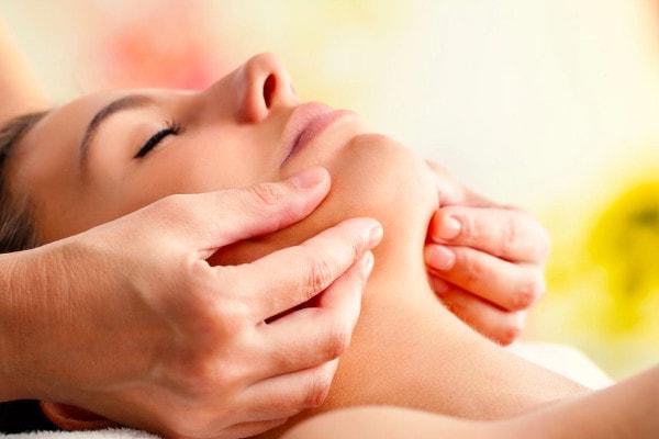 Une femme allongée sur une table de massage se fait masser le bas du visage par une masseuse