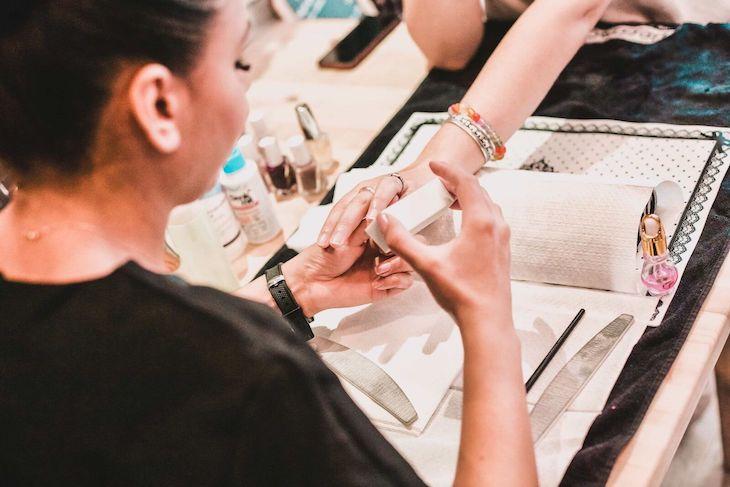 Une esthéticienne est en train de limer les ongles de sa cliente