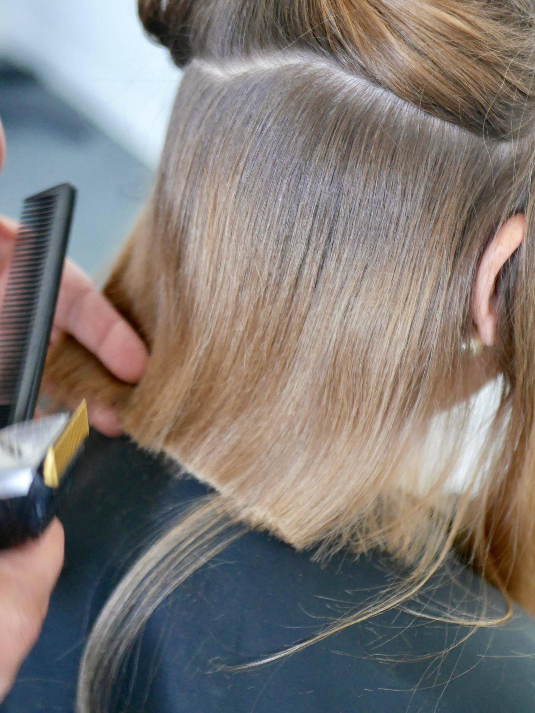 jeune femme se faisant couper les cheveux par sa coiffeuse à domicile