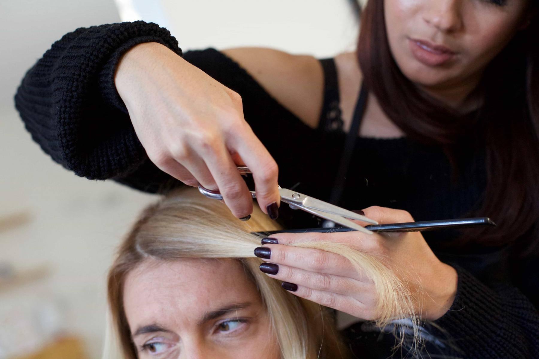 coiffeuse fait la frange de sa cliente