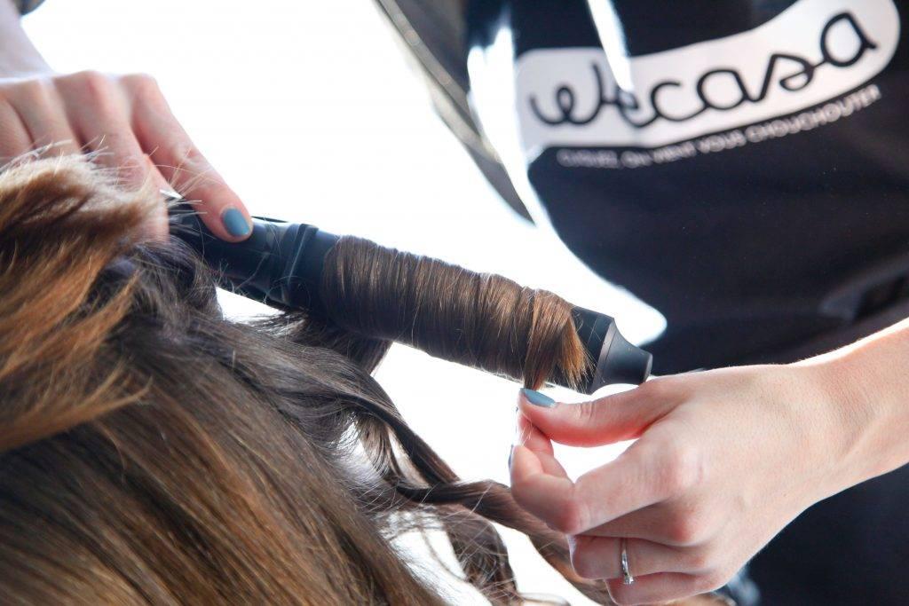 coiffeuse réalise un wavy avec un fer à boucler