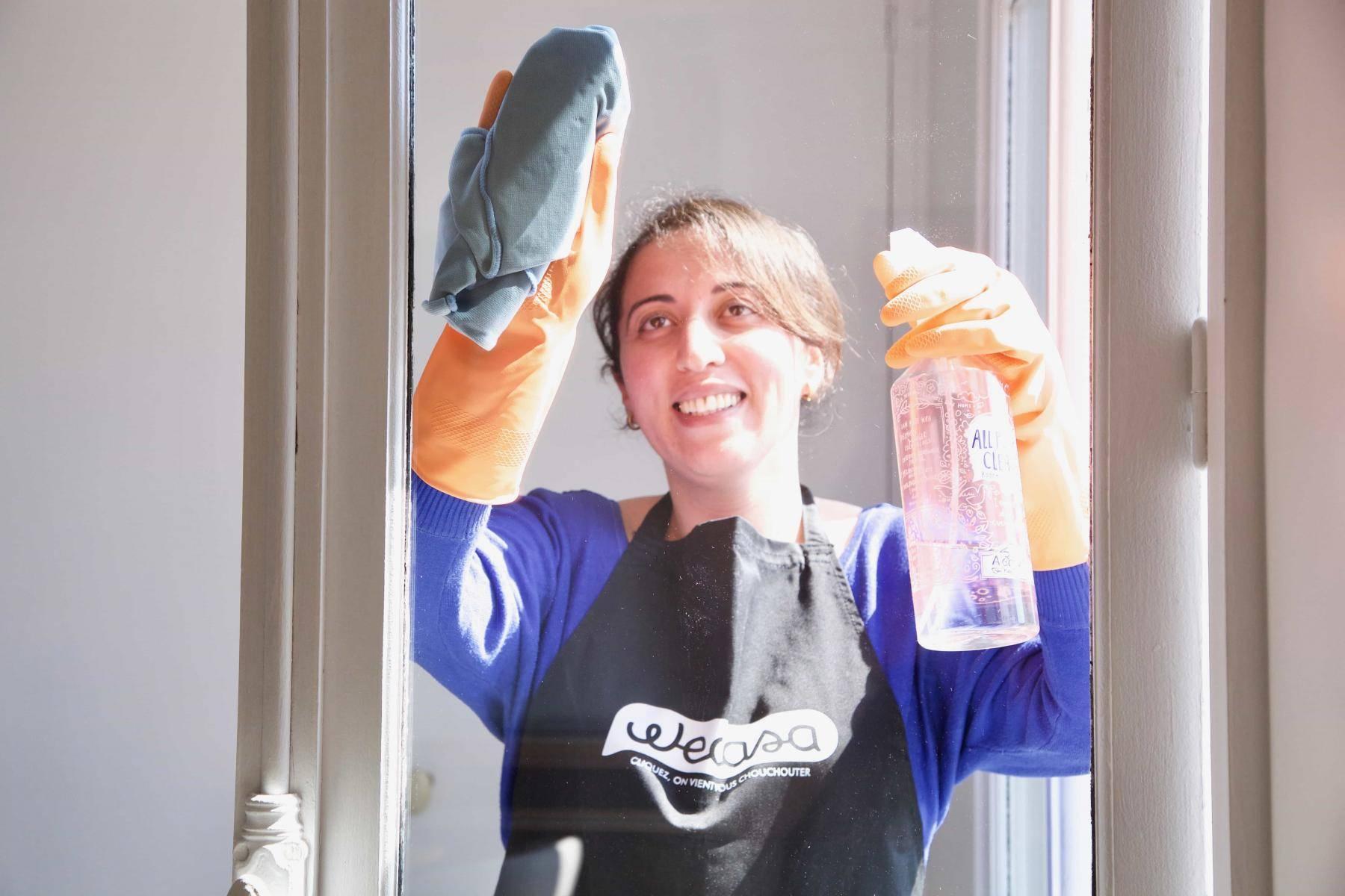 une femme de ménage passe le produit pour les vitres