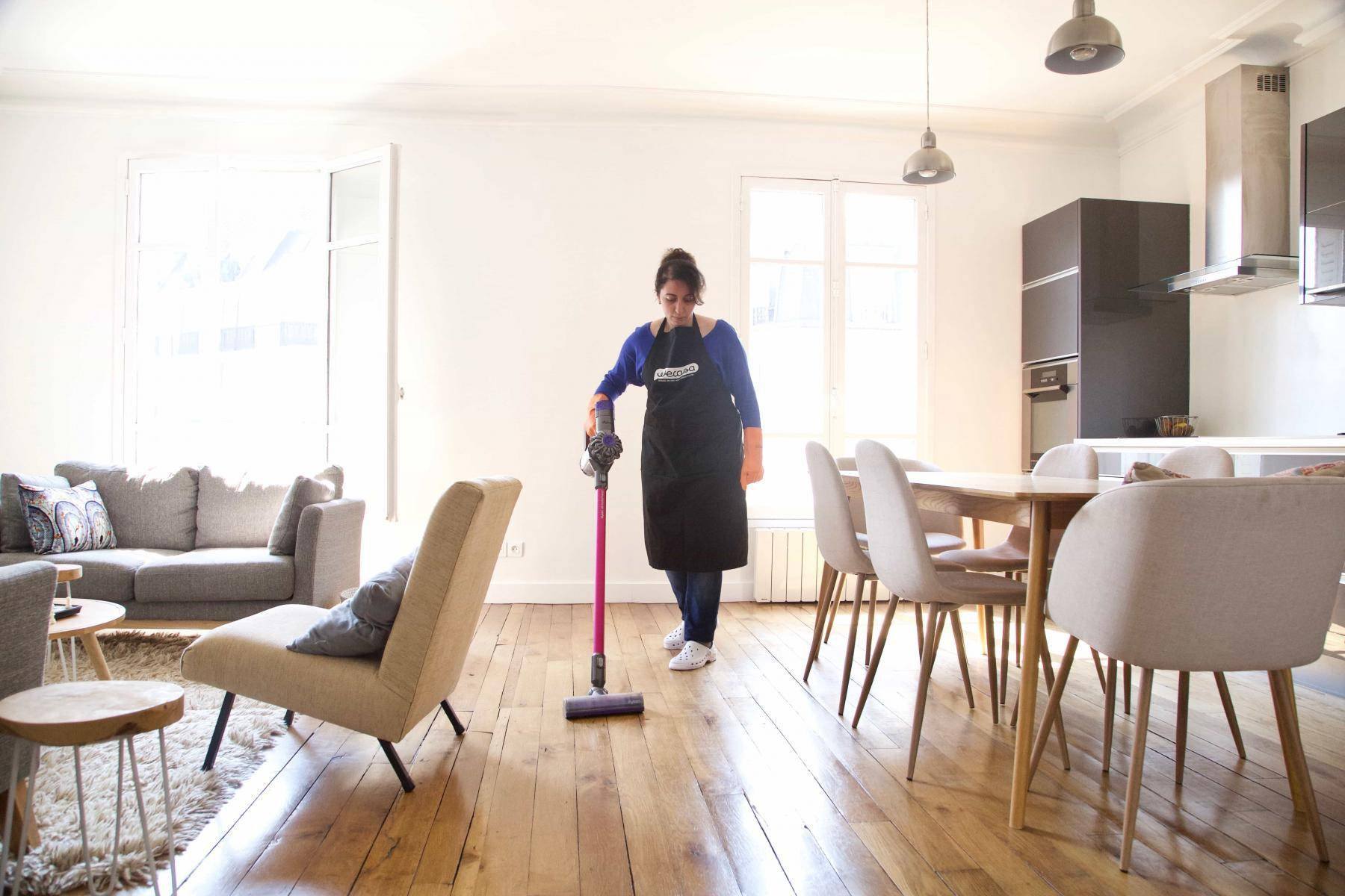 une femme de ménage wecasa passe l'aspirateur