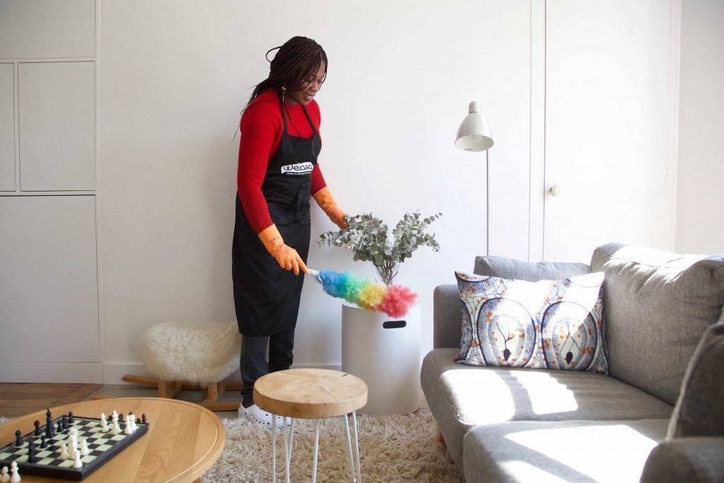 une femme de ménage fait les poussières