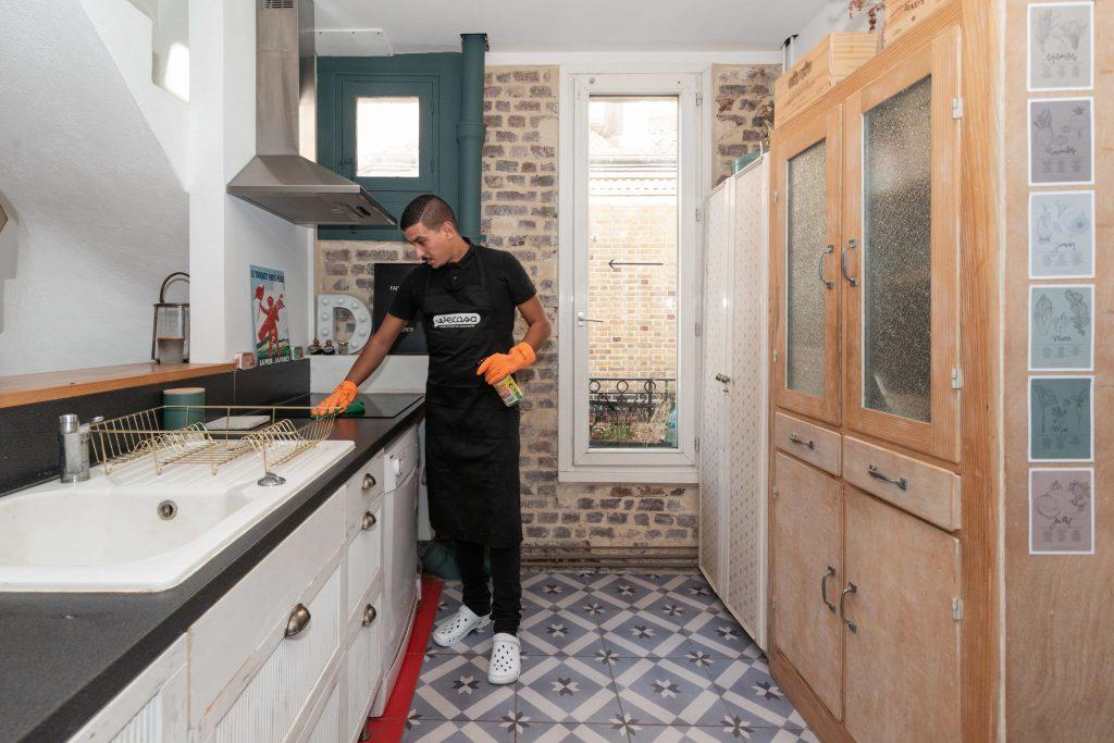 homme de ménage nettoie cuisine avec vinaigre blanc
