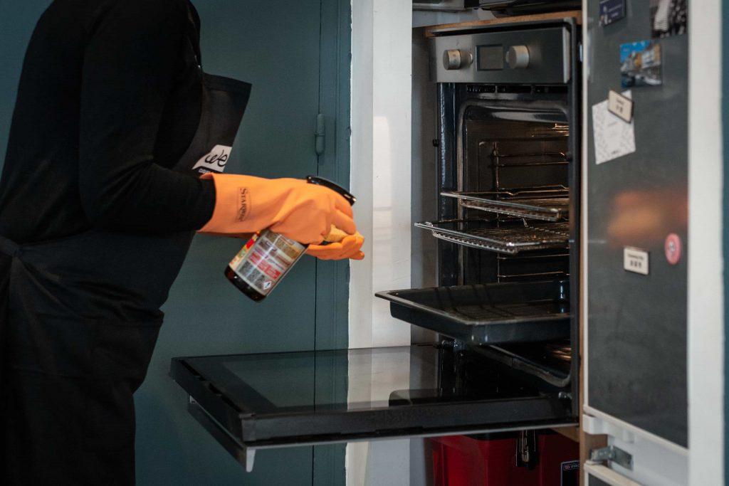 femme de ménage nettoie four