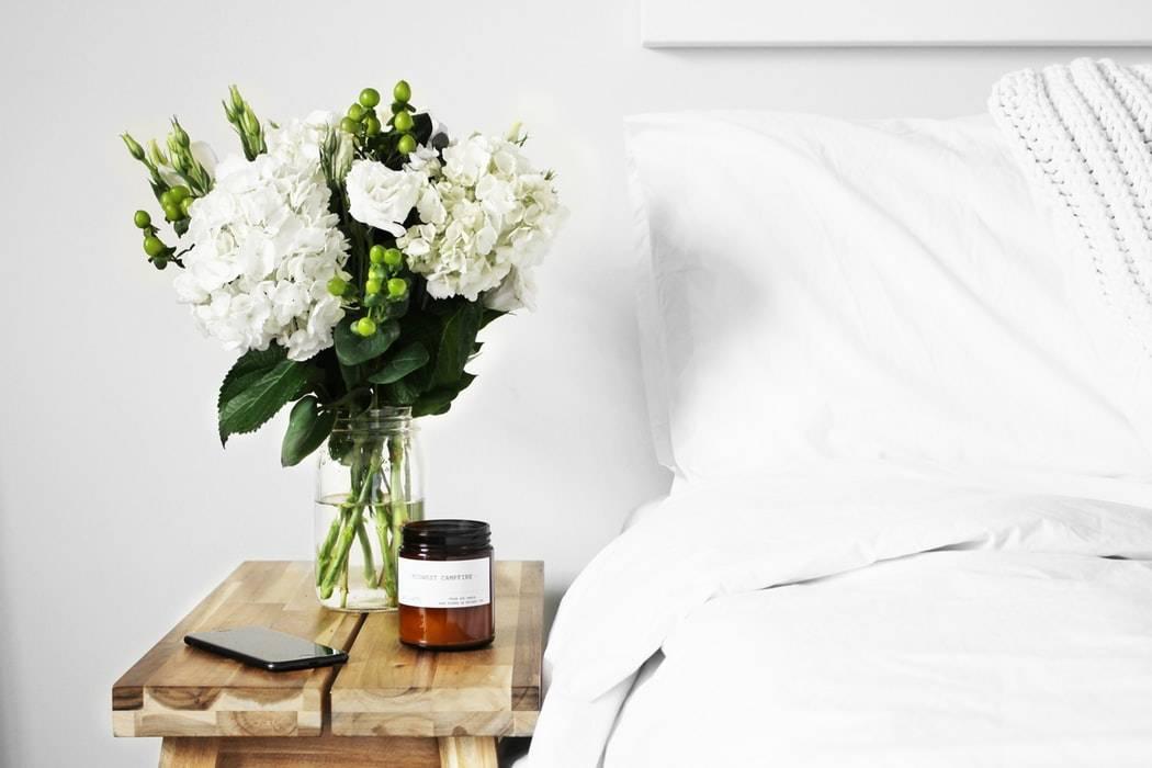 Bouquet de fleurs blanches sur une table de chevet en bois avec une bougie parfumée, des draps et un mur blancs