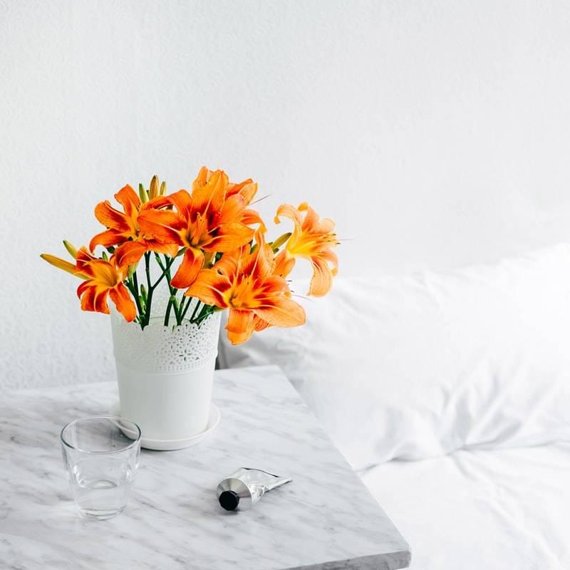 Bouquet de fleurs oranges sur une table de chevet en marbre, des draps et un mur blancs