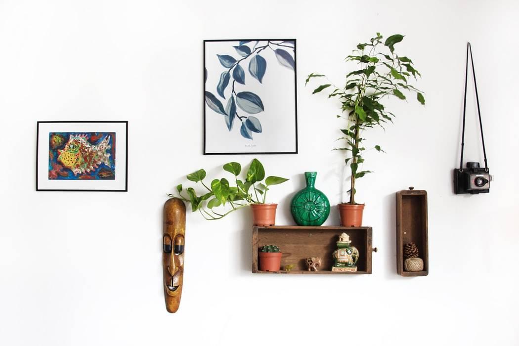 Décorations murales avec des tableaux, des étagères en bois, des plantes, un masque et un appareil photo