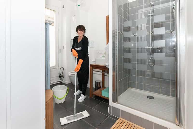 image d Aide-menagere nettoyant le sol de la salle de bain